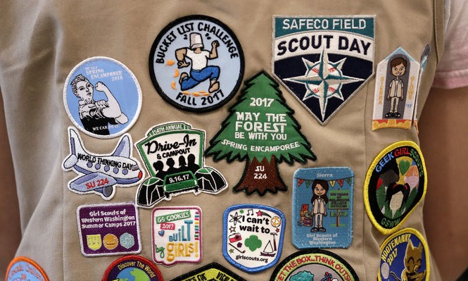 "FILE - In this June 18, 2018, file photo, patches cover the back of a Girl Scout's vest at a demonstration of some of their activities in Seattle. The Girl Scouts of the United States of America filed a trademark infringement lawsuit on Monday, Nov. 5, against the Boy Scouts of America for dropping the word ""boy"" from its flagship program in an effort to attract girls. (AP Photo/Elaine Thompson, File)"