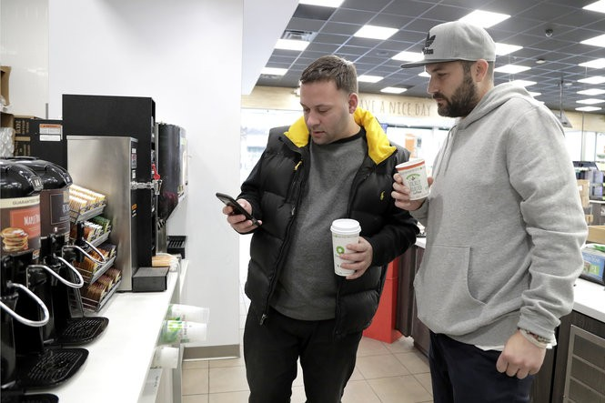 Lenny Sciascia, left, and Mario DeAngelis check if the lines have changed on the sporting events Sciascia just placed bets on while grabbing coffee at a gas station before heading back to his home in Staten Island, N.Y. (AP Photo | Julio Cortez)