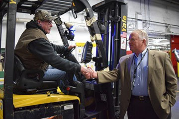 Keith Campbell, chairman of the board at Mannington, shakes hands with one of the forklift drivers.