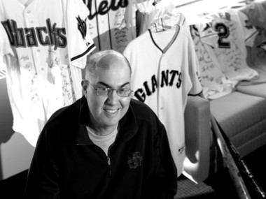 Michael Weiner, head of the MLB Players Association, poses in his Manhattan office with 28 jerseys and two bats representing all 30 Major League Baseball teams. They were signed by all the players and presented to him as a show of support in his battle with cancer.
