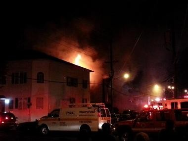 Flames shoot out of the roof of a New Brunswick home on Baldwin Avenue Saturday night.