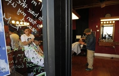 Barbers Neurys Estrella and Daren Perez of Rutgers Barber Shop, one of the more than 25 businesses to participate in the Highland Park Gratitude Graffiti project.