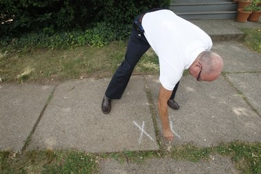 """Scott Luthman, director of code enforcement, marks an """"X"""" on the pads that need to be replaced by a resident on Wayne Street, as the borough-wide program began in 2012."""