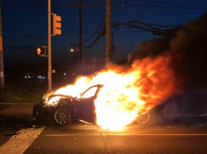 A 59-year-old woman was pulled from her burning car by a passing off-duty corrections officer following a two-vehicle collision in Sunday night in South Brunswick.