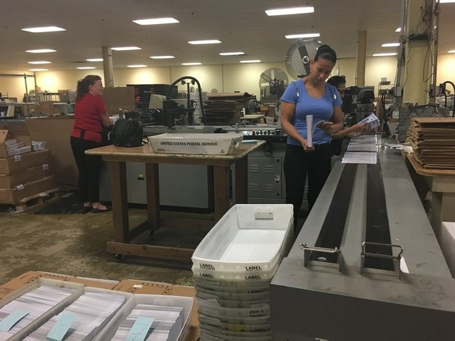 Universal Mailing Service workers process unrelated mailers on the same machine used to process vote by mail ballots. (Cassidy Grom | For NJ.com)
