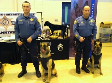 Morris Sheriff's Detectives Mike McMahon, left, and Frank Perez, stand with their dogs, Ronan and Zander, wearing their new bullet-proof vests.
