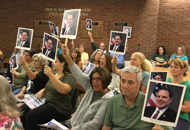 Residents holding photos of late Rockaway Township Mayor Michael Dachisen at a council meeting, Sept. 14, 2018.