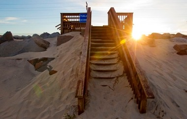 The sun sets over the sea wall in Sea Bright, where the U.S. Army Corps of Engineers recently performed a scheduled beach replenishment without building massive sand dunes.