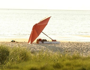 A beach umbrella rises from the sand along Sandy Hook Bay. The Gateway National Recreation Area, including Sandy Hook, was created by Congress 40 years ago in 1972, and the Sandy Hook lighthouse has been guiding ships through New York Harbor since 1764.