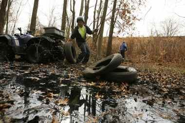 Workers from the Morris County Mosquito Commission remove discarded tires from a wooded area in Denville in this file photo. Experts say each tire has the potential to breeds hundreds of thousands of mosquitoes. (Star-Ledger File Photo)
