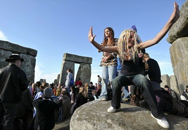 Revelers celebrate as the sun rises behind Stonehenge in England during the annual summer solstice festival. The festival, which dates back thousands of years, celebrates the longest day of the year, when the sun is at its maximum elevation. (Carl Court | Getty Images)