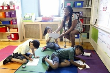 Roseville Community Charter School second grade teacher Danielle Cofield helps Briana Azcona, center, as she works on a project with classmates Ian Santana, left, and Samiyah Bennett during a four-week summer intensive program.