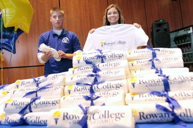 Gloucester County College (GCC) student Vanessa Brown, holds up a t-shirt with the new Rowan College at Gloucester County logo after Rowan University and Gloucester County College signed a partnership agreement, Friday, Jan. 10, 2014. Under the partnership Gloucester County College will change its name to Rowan College at Gloucester County. To the left is GCC student Frank Bilodeau. (Staff Photo by Tim Hawk/South Jersey Times)
