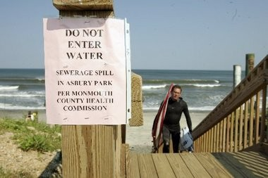 In this 2007 file photo, Ben Hamilton of Fair Haven climbs the stairway at the Darlington Avenue beach in Deal as a pink sheet of paper from the Monmouth County Health Commission warns patrons that the beach is closed due to a sewage spill in Asbury Park.