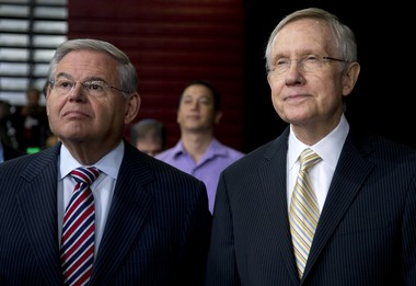 Senate Majority Leader Harry Reid of Nev., right and Senate Foreign Relations Committee Chairman Sen. Robert Menendez, D-N.J., left, look to President Barack Obama as he speaks about immigration at Del Sol High School, in Las Vegas, Friday, Nov. 21, 2014. The president unveiled expansive executive actions on immigration, the previous night, to spare nearly 5 million people in the U.S. illegally from deportation, setting off a fierce fight with Republicans over the limits of presidential powers.