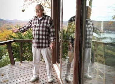 Bob Ehling on the balcony where he shot a bear last October as it pawed at the sliding glass door behind which his wife was sitting. The bear had to climb up a four-by-six beam to get to the 15-foot-high deck.