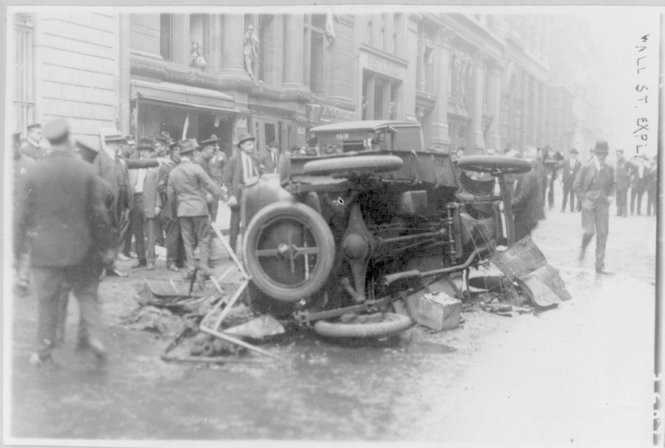 Wall Street explosion, 1920. Automobile lying on its side in foreground. The bombing was believed to be inspired by an Italian anarchist. (Library of Congress)