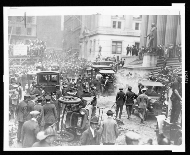 A crowd gathered following the explosion on Wall St.,a car overturned in foreground, an ambulance behind it. Photo taken Sept. 16, 1920 (Library of Congress)