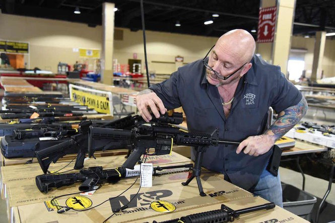 Keith Moreau sets up his gun display on Feb. 16, 2018 during preparations for the February 17-18 South Florida Gun Show at the South Florida Fairgrounds in Miami, Florida. The gun show starts three days after a mass shooting 30 miles away at the Marjory Douglas High School in Parkland, Florida. Vendors said they were expecting a big turnout and sales, and because of the shooting there will be a panic regarding gun restrictions and new laws that could be put in place. Vendor Domingo Martin said he brought his entire stock of of 42 AR-15's, adding that he is not the only one selling the unit at the weekend show.