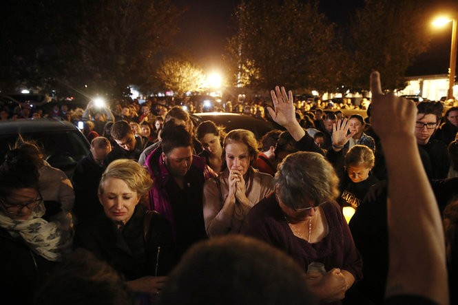 People gather outside a coffee shop for a vigil for one of the victims killed in last week's mass shooting at the Borderline Bar and Grill in Thousand Oaks, Calif. (Jae C. Hong | Associated Press)