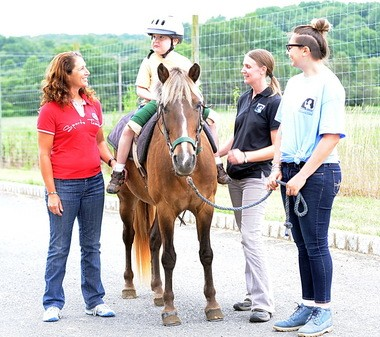 Catherine Haddad Staller with Mane Stream client Trey Mittuch, 9, of Highland Park; occupational therapist Gina Taylor and volunteer Valeria Cogliani.