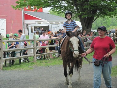 Friends' member and volunteer Cheri Milos leads a young rider on Hercules during Family Fun Day at Lord Stirling Stable.