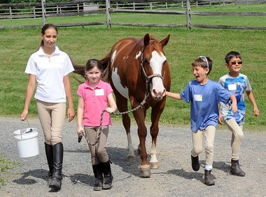Ava Laufhutte, Tess Coffey, Luc and Dax Bush go back to the barn at Mane Stream after a grooming session with Tink the pony.