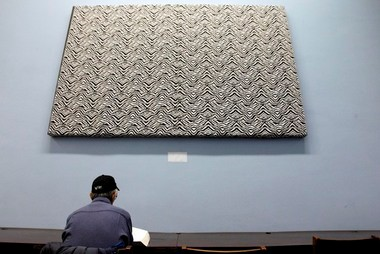 A Newark Library patron sits under a piece of artwork by Kara Walker, covered by a zebra-print cloth. The drawing was covered after employees of the library complained about the image, which depicts a slave performing oral sex. The painting is once again uncovered.