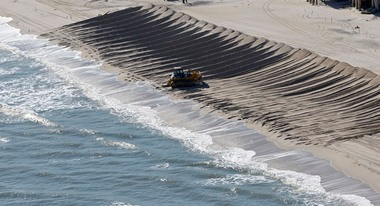 A bulldozer pushes sand to create temporary dunes after Hurricane Sandy destroyed in Ortley Beach.