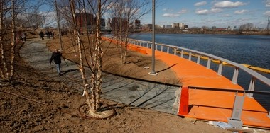 Joseph Nardone carries his camera down to the water's edge of the Passaic River to take pictures for the latest installment of Riverfront Park currently under construction. The new seven acre addition is part of the city's continuing plan to beautify the area along the Passaic River.