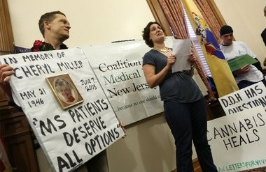Jay Lassiter, left, a patient and advocate, listens to Meghan Wilson talk about her two-year-old daughter Vivian's seizures during a press conference on the slow implementation of New Jersey's medical marijuana program.
