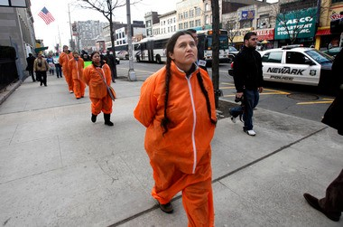 Immigrants and human rights advocates including Diana Mejia, who is wearing an orange jump suite to represent detainees, walk three miles from the Immigration and Customs Enforcement offices in downtown Newark to the Essex County Correctional Facility. The February 2011 march highlighted opposition the planned addition of 2,700 immigration-detention beds to what they said were already crowded and inhumane facilities.