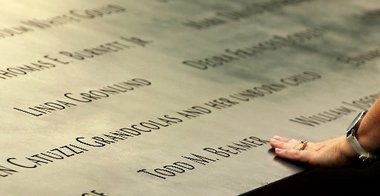 A visitor touches Todd Beamer's name at the 9/11 Memorial.