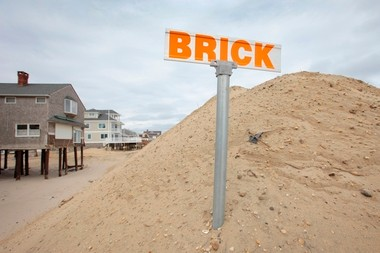 A sign designating the southern border of Brick Twp. sticks out the top of a fifteen foot high sand dune adjacent to beachfront homes that were damaged during Hurricane Sandy. Brick, NJ 2/22/13