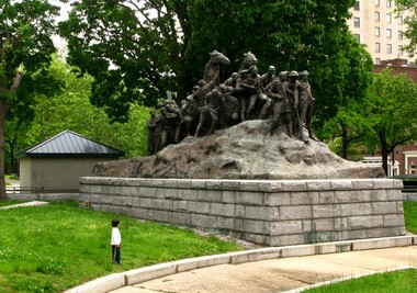 A small boy gazes up at the colossus, Wars of America, in Military Park, Newark