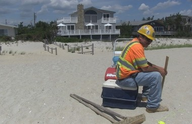 A worker takes his lunch break from the job of repairing the beach public access walkway damaged by Hurricane Sandy in Harvey Cedars, New Jersey, directly in front of the home of Phyllis and Harvey Karan, who refused to sign an easement for the construction of a dune in front of their property.