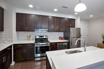 Apartments feature kitchens with stainless-steel appliances, hardwood flooring and tiled backsplashes.