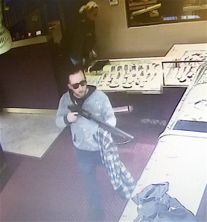 A woman police allege is Emily K. Lopazanski can be seen near the counter as accused accomplice Marc Niedle waves a shotgun, cops said. (Wayne PD)