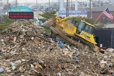 A bulldozer contracted by Florida-based AshBritt Inc. piles debris being collected in a temporary dump at the base of the Rt. 37 bridge in Seaside Heights. Even before Hurricane Sandy struck, the Christie administration was fast-tracking a $100 million no-bid contract for the politically-connected firm known for cleaning up the wreckage left by natural disasters.