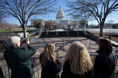 Tourists snap photos of the Capitol, where preparation continues Saturday for the second inauguration of President Obama. The public ceremony will take place Monday.