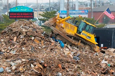 A bulldozer contracted by AshBritt, Inc. piles debris being collected in a temporary dump at the base of the Route 37 bridge in Seaside Heights in the wake of Hurricane Sandy's destruction.