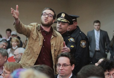 Police approach Rowan University student Michael Brein from Bellmawr as he heckles Gov. Chris Christie during Thursday's town hall meeting at the YMCA of Burlington County in Mount Laurel.