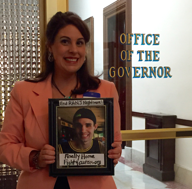 """Longtime Hunterdon County resident Rita O'Grady poses outside the governor's office with a homemade sign bearing her son's photo following the Assembly's vote Thursday to end the """"Return Home New Jersey"""" policy that began in 2009. (Photo Courtesy of Rita O'Grady)"""