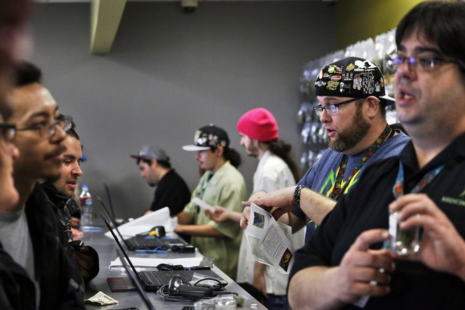 """Employees help customers at the crowded sales counter inside Medicine Man marijuana retail store, which opened as a legal recreational retail outlet in Denver on Wednesday, Jan. 1, 2014. Colorado began retail marijuana sales on Jan. 1, a day some are calling """"Green Wednesday."""" (AP Photo/Brennan Linsley)"""