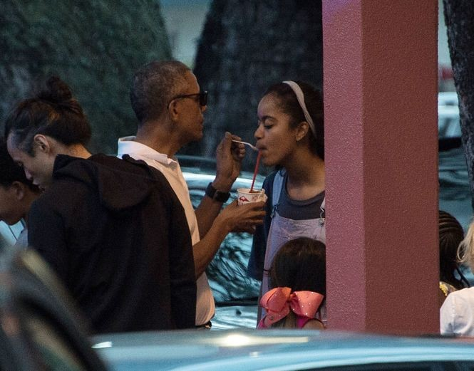 US President Obama gives his daughter Malia a taste of his shave ice at the Island Snow parlor in Kailua, Hawaii, on December 24, 2016. / AFP PHOTO / NICHOLAS KAMMNICHOLAS KAMM/AFP/Getty Images
