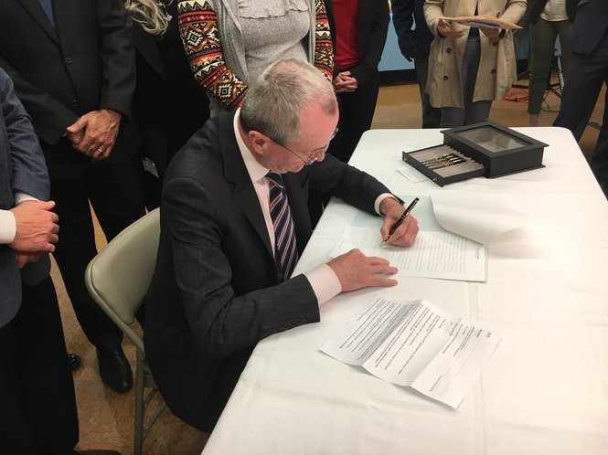 Gov. Phil Murphy signs an executive order on gun safety Friday at Asbury Park Middle School.