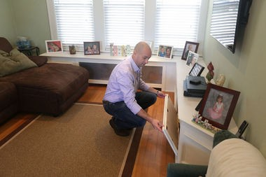 Hugh McAleavy shows off the fold-out cabinets in the living room's new entertainment center.(John O'Boyle   NJ Advance Media)