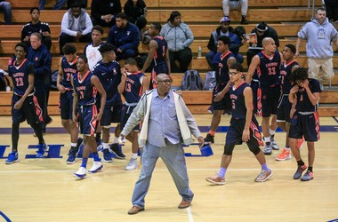 Paterson Eastside head coach Juan Griles (center) and his team walk onto the court during a game last week.