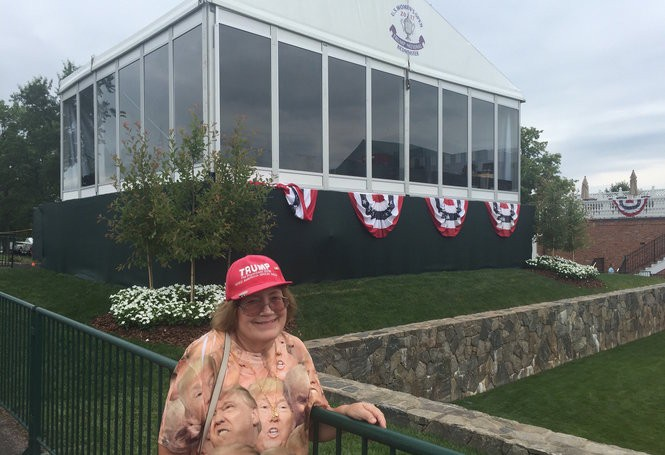 "Susan Torbyn, wearing a Trump T-shirt that she bought at a flea market for $20, stands near the ""skybox"" where the president is expected to watch the U.S. Women's Open."