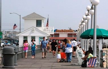 Beach-goers stroll along the boardwalk, toward the pavilion, in Avon-By-the-Sea in this file photo from May 2009. The pavilion was destroyed by Hurricane Sandy in October 2012.